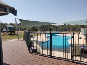 Showing Shade by a sunsail over a swimming pool
